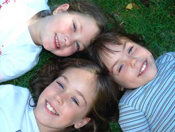 Oviedo Dentist Group of children lying on grass smiling